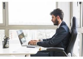 在工作场所使用笔记本电脑的年轻商人_3156895