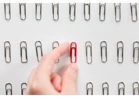 在金属回形针中手工挑选一种红色的回形针_1281786