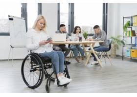 坐在轮椅上的妇女在办公室用手机工作_7772344