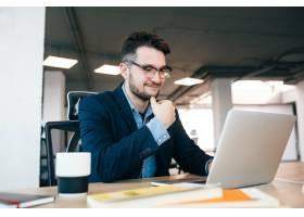 办公室的桌子旁一位迷人的黑发男子正在用_9960950