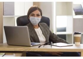 办公室里戴着口罩的女商人的正视图_10337418