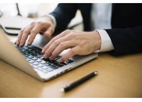 办公室里的一名男子在笔记本电脑上打字_1465350