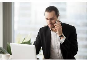 办公室里的年轻商人看着笔记本电脑_4013282