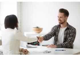 千禧一代的合作伙伴微笑着在办公室握手感_3939761