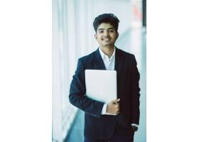 印度快乐商人在办公室使用笔记本电脑的肖像_9076246