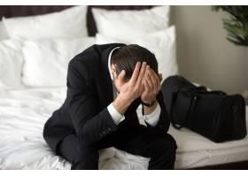 压力很大心烦意乱的商人坐在床上头疼_4013397