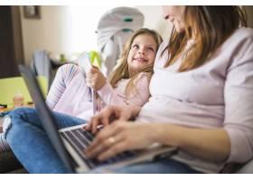 可爱的微笑着的女孩用笔记本电脑看着她的母_2602063