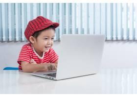 可爱的男孩在孩子们的房间里玩LABTOP_1285553