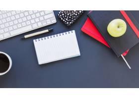 咖啡杯和苹果旁边有记事本和键盘_5471489