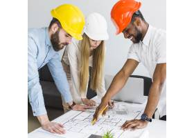 一群建筑师在办公室里讨论平面布置图_2593068