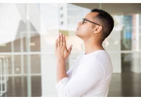 严肃的男人闭着眼睛把手放在祈祷的姿势_4999685