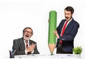 两位同事一起在办公室里用巨大的铅笔工作_7021005