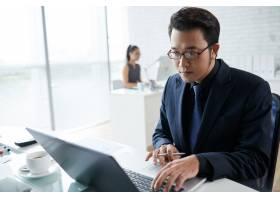 亚洲商人在协同工作空间使用笔记本电脑工作_5839824