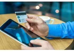 使用信用卡和数字平板电脑在线购物的商人_1192408