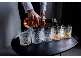 一个人正在往杯子里倒烈性酒_7251121