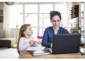 一个女孩坐在木桌上看着她的母亲在笔记本电_2627483