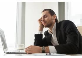 一位年轻的商人上班时在笔记本电脑前打瞌睡_4013323