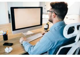 一位年轻的黑发男子正在办公室的台式电脑前_9960983