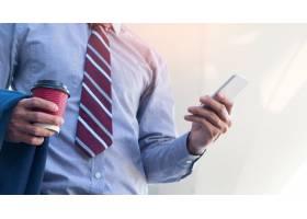 一位年轻而成功的商人正在智能手机上阅读一_1203153