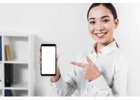 一位快乐的亚洲年轻女商人指着手机的肖像_4157501