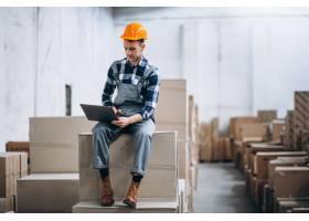 一个年轻人在仓库里搬运箱子_5578218