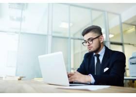 一位在办公室使用笔记本电脑的商人_5400235