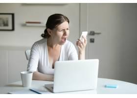 一位妇女坐在办公桌前手持笔记本电脑看_1281129