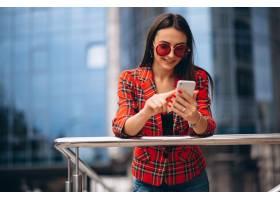一位年轻女子在办公中心边讲电话_4201948
