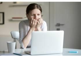 一位年轻女子坐在办公桌前拿着笔记本电脑的_1281128