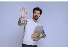 一位拿着项目文件夹的商人与他的同事握手打_13406794