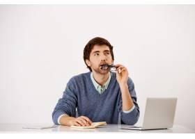 一位深思熟虑的商人坐在办公桌前咬着眼镜_9226811
