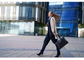 一位穿着外套和西装的女商人手里拿着一个_10450834
