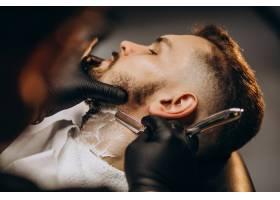 一位英俊的男子在理发店剪胡子_7435502