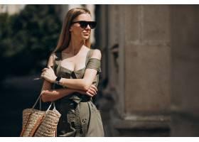 一位身穿绿色连衣裙的年轻女子站在那座老建_5495912