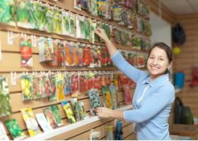 一名女子在商店里选择包装好的种子_1489331