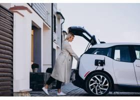 一名女子在她的房子旁给电动车充电_6213703
