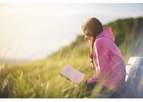 一名女性坐在长凳上在草地上阅读圣经的特_9184692