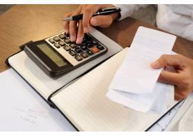 一名妇女在计算器上计算账单的特写_3077822
