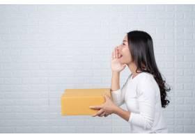 一名妇女拿着一个棕色的邮筒用手语做手势_4284240