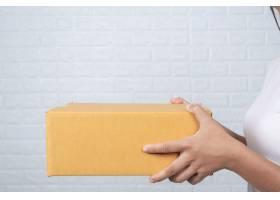 一名妇女拿着一个棕色的邮筒用手语做手势_4284241