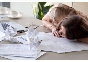 一名妇女睡在铺满皱巴巴的纸的桌子上_3938713