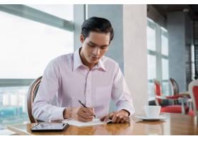 一名年轻的亚洲男子在咖啡馆写作_993783