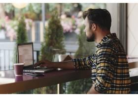 一名男子在咖啡厅使用笔记本电脑_3623432