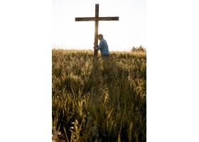 一名男子在草地上用头靠在木制十字架上的垂_8943602