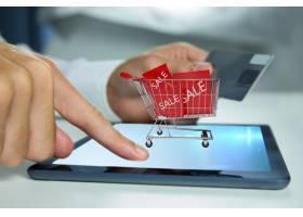一名男子推着购物车玩平板电脑_926676