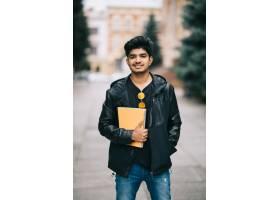 一名英俊的印度年轻学生站在街上手里拿着_9077333
