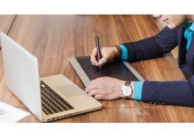 一名西装革履的男子坐在办公桌前画画_1302674