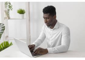 一名非洲裔美国男子在笔记本电脑上工作_11235005