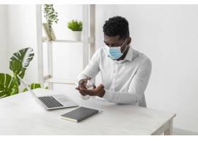 一名非洲裔美国男子戴着口罩洗手_11235016