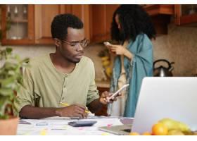 年轻的黑皮肤丈夫坐在餐桌旁拿着文件计_9534754